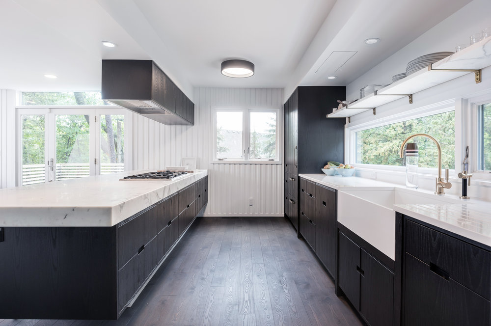 Modern kitchen renovation with dark cabinetry and thick marble countertop