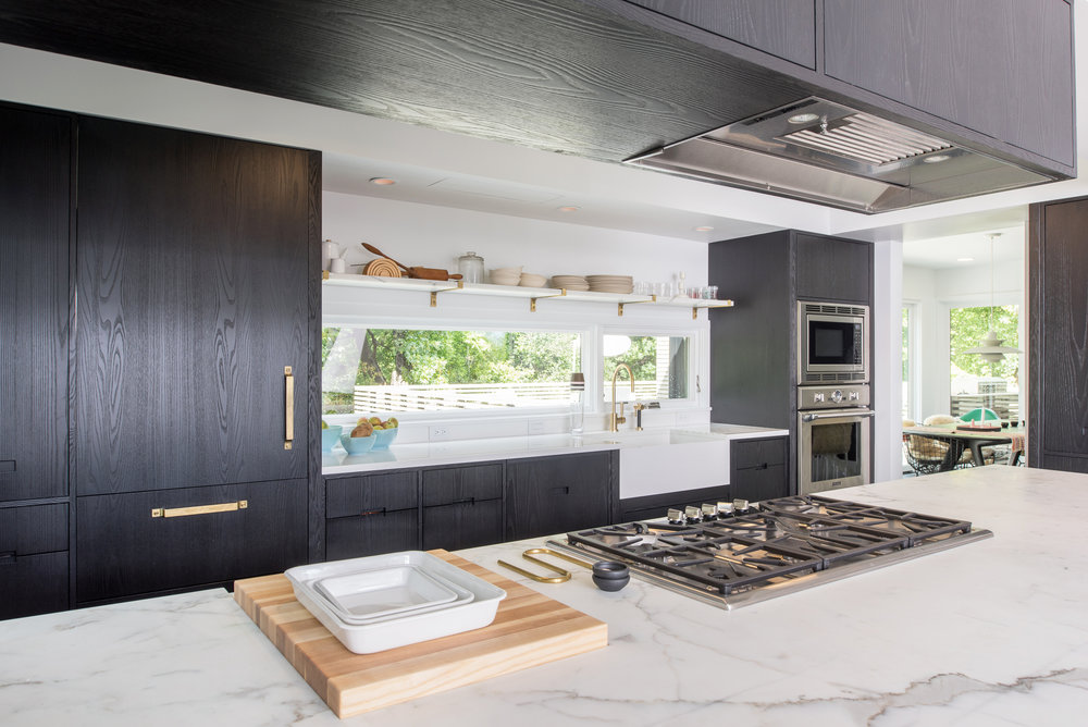Modern kitchen remodel detail of marble countertop and brass hardware