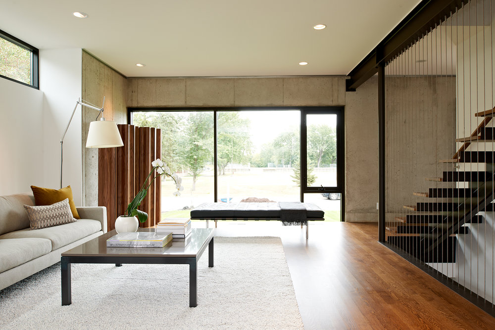 Modern living room with wood floor, concrete wall, and custom open stair