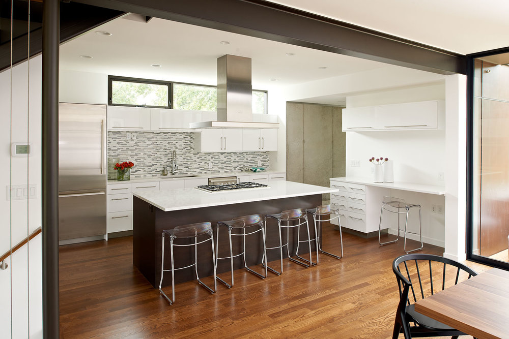 Modern bright kitchen with white cabinetry and center breakfast bar