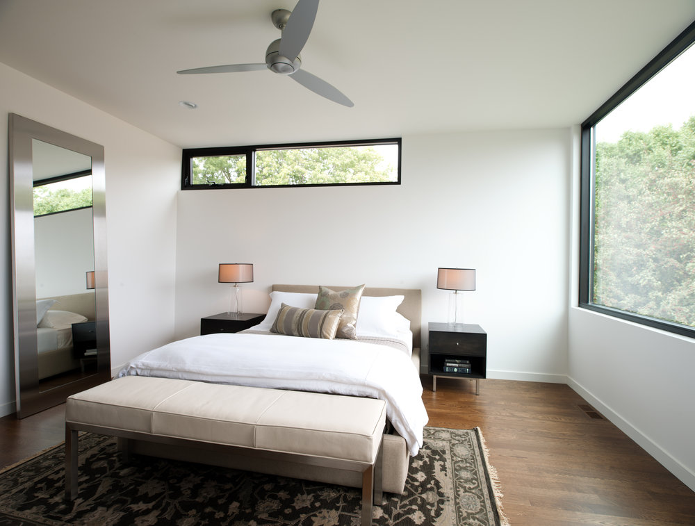 Modern white bedroom with large windows