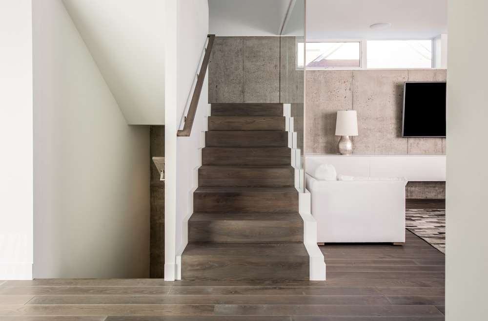 Wood staircase against an exposed concrete wall