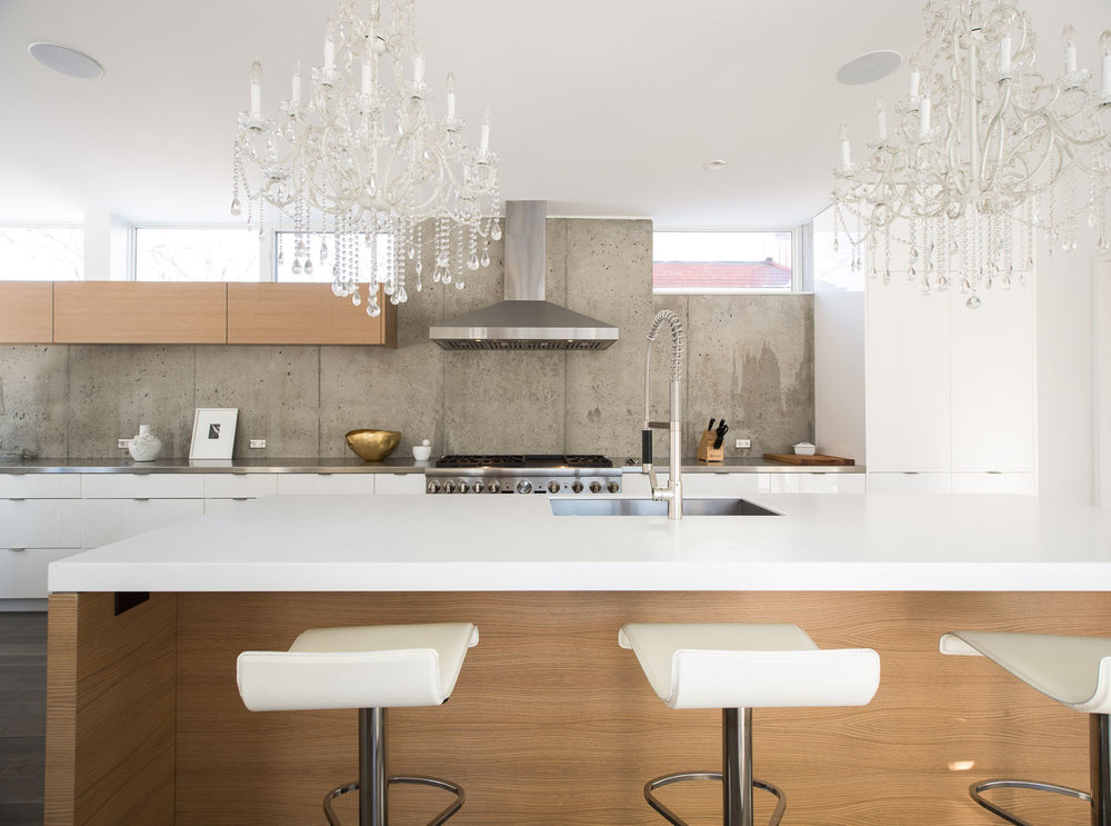 Modern kitchen with mixed white and wood cabinetry and exposed concrete walls