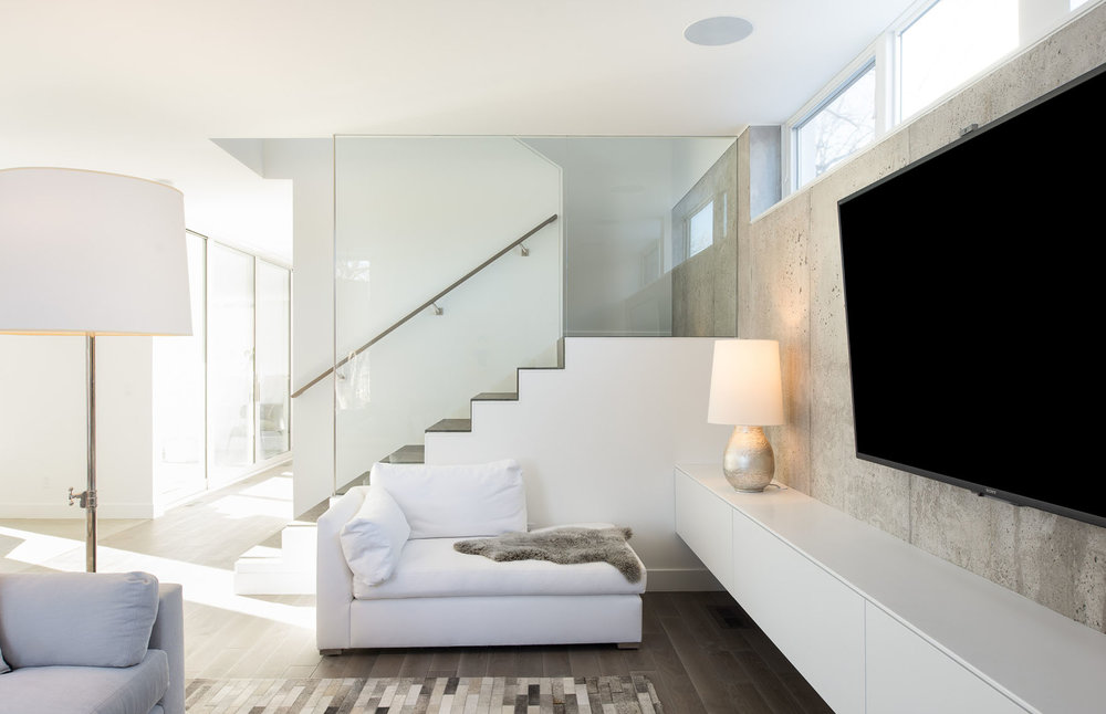 Modern living room with exposed concrete and a glass stair divider