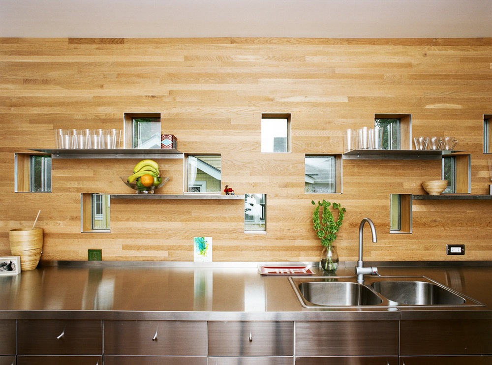 Kitchen counter with steel top and wood backsplash and custom windows