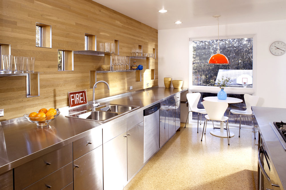 Modern kitchen with steel counter and wood backsplash