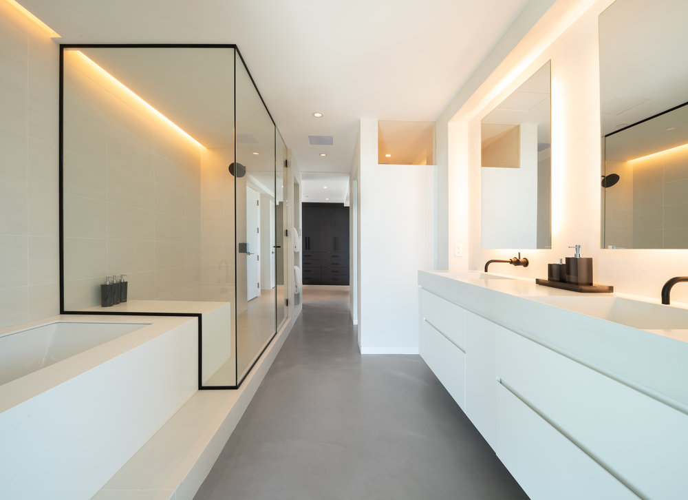 Modern white bathroom with walk-in shower and light cove detail