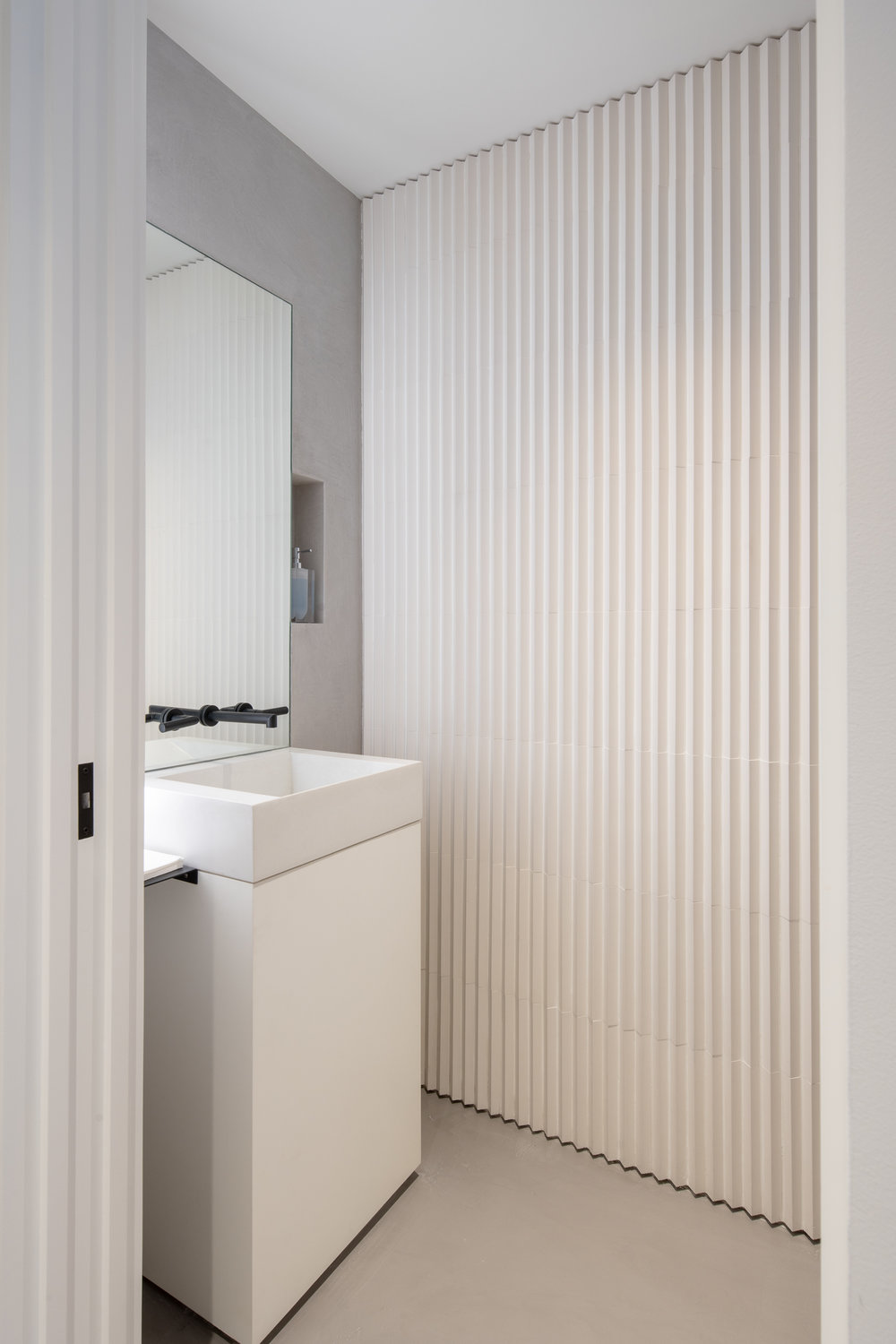 Modern powder room with geometric tile wall and custom soap niche
