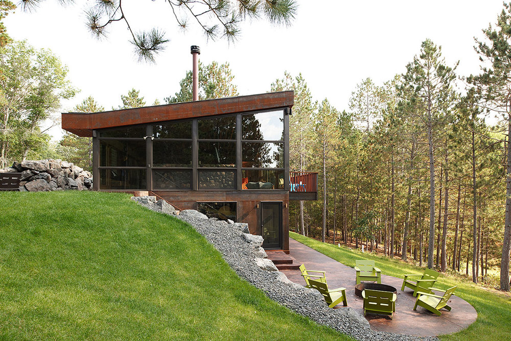Modern cabin with large windows and exposed basement