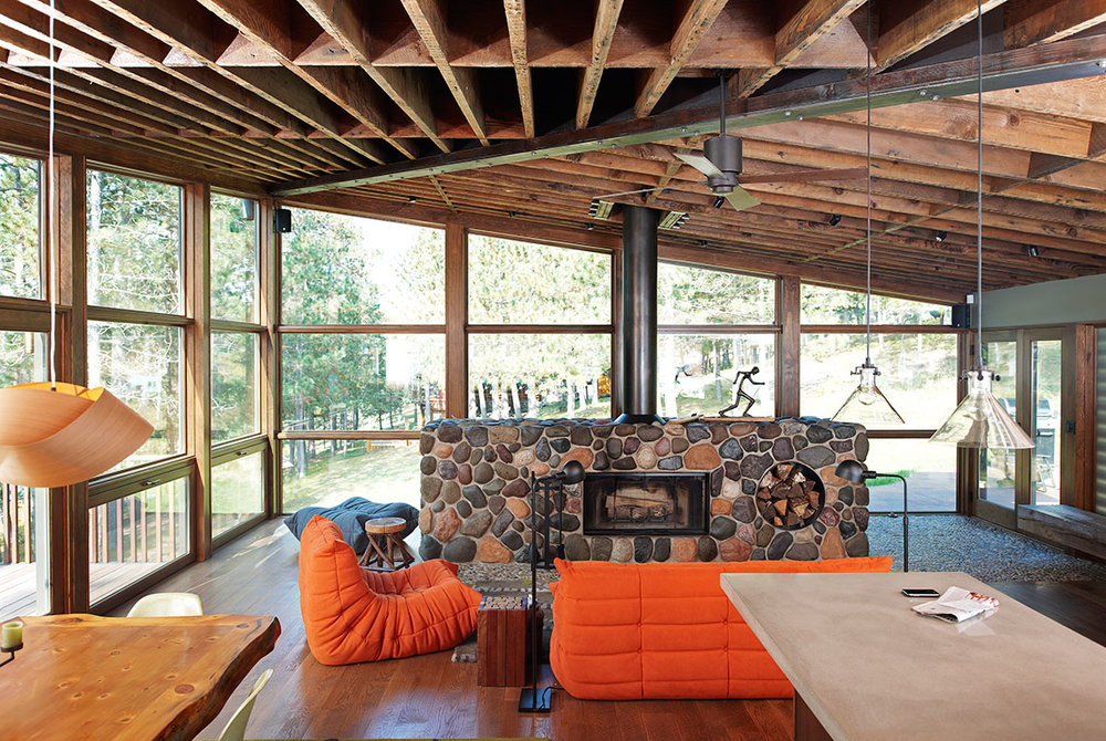Center pebble fireplace with reclaimed timber ceiling in a cabin living room