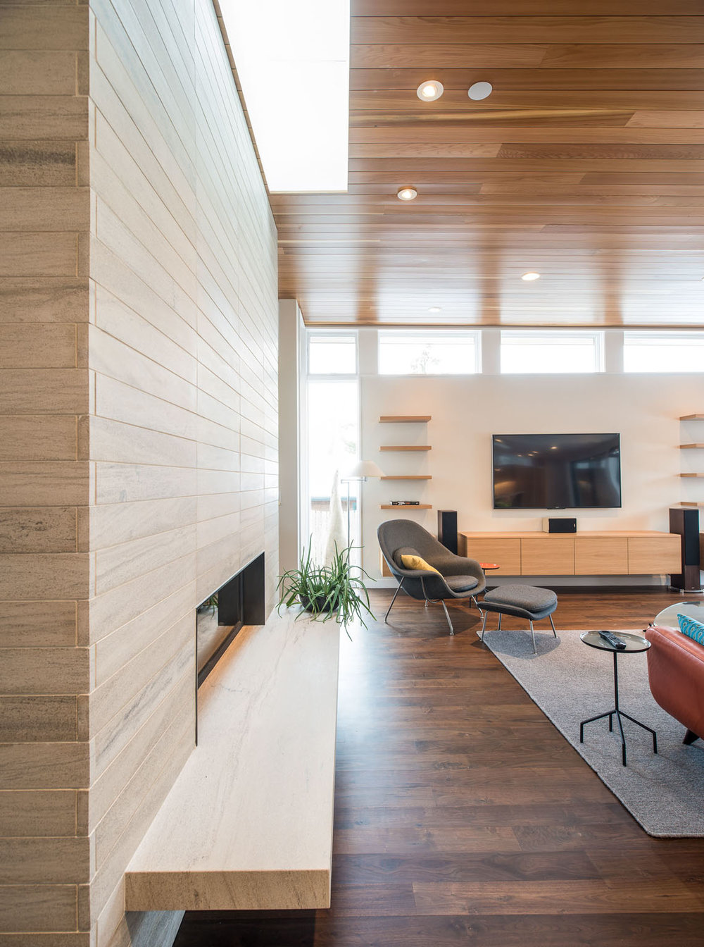 Modern stone fireplace detail with corresponding wood paneled ceiling