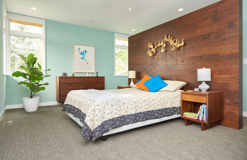 Midcentury master bedroom with custom headboard wall