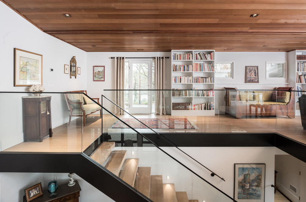 Floating tread stair with modern steel and glass handrails