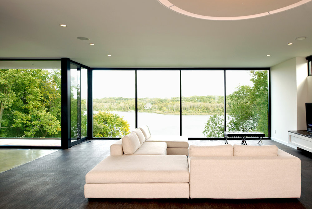 Modern minimal living room with glass wall to outdoors