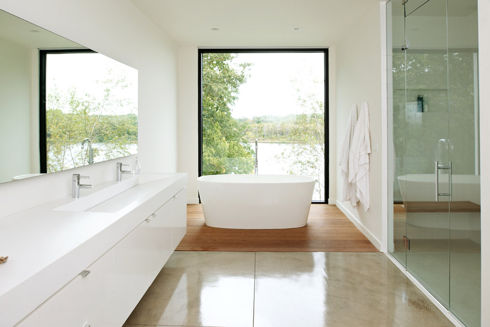 Minimal white master bathroom with soaking tub and picture window