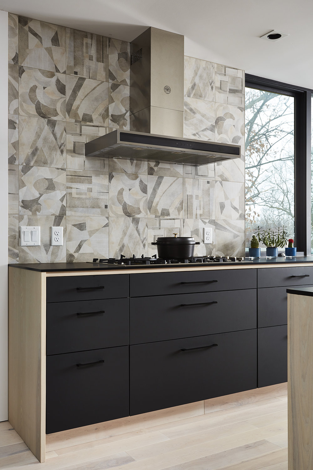 Black and wood cabinetry detail with graphic backsplash tile behind range