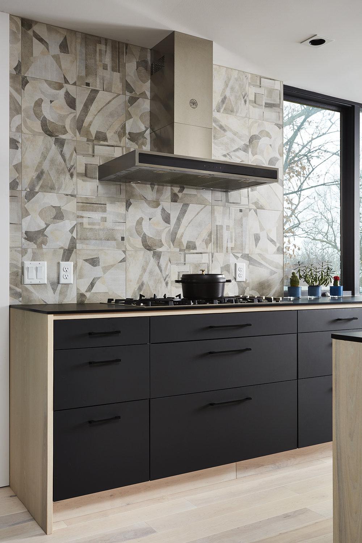 Black and wood cabinetry detail with graphic backsplash tile behind range