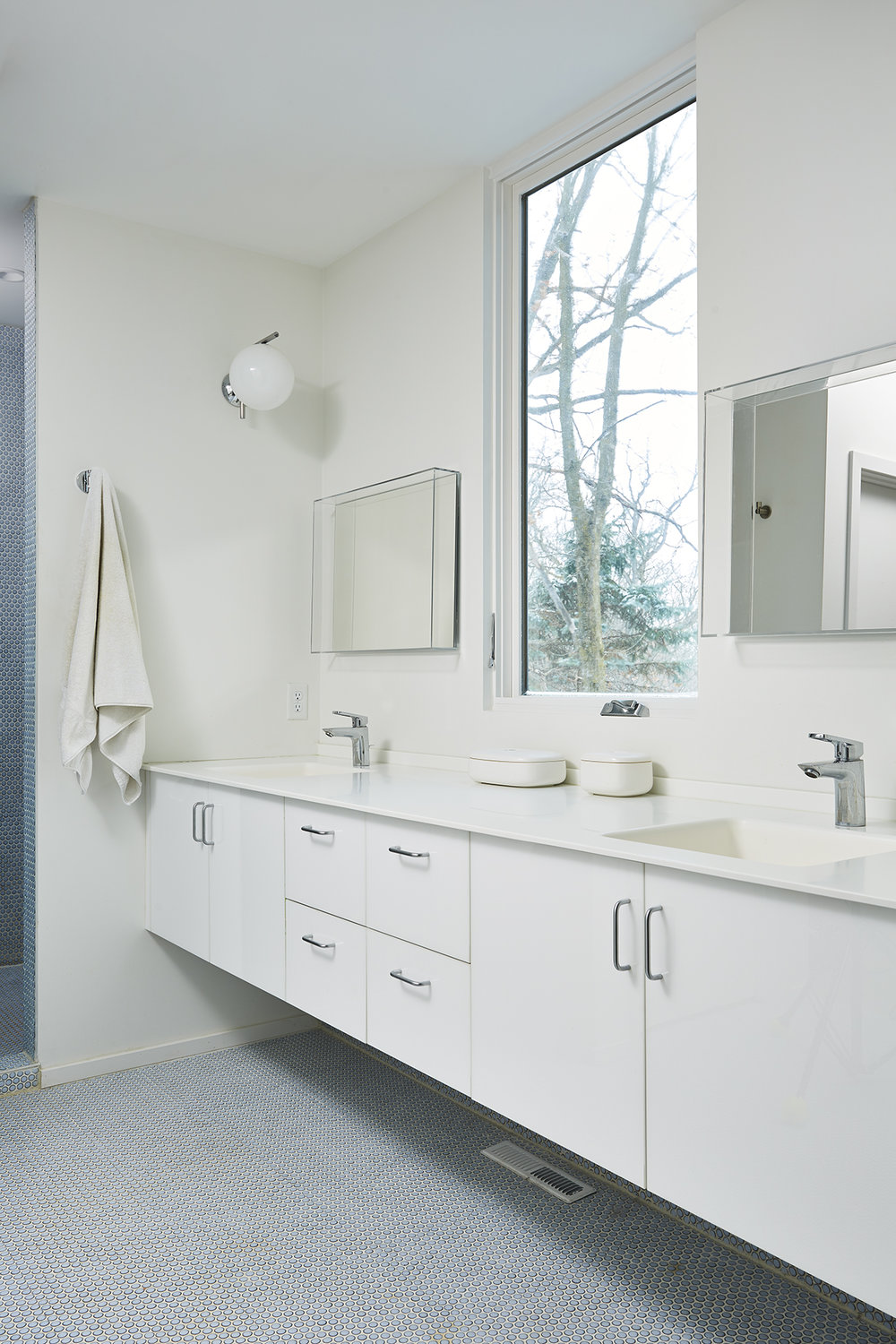 Custom floating master bathroom vanity with blue penny tile floors and shower surround