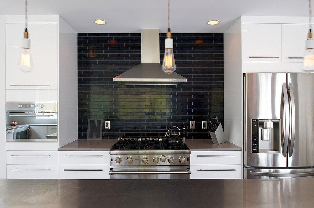 Modern monochromatic kitchen renovation with white cabinetry and black subway tile backsplash