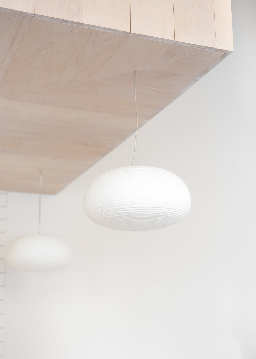 custom wood ceiling detail with white pendant lights