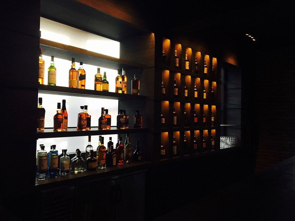 modern custom wood bar and back-lit bottle display