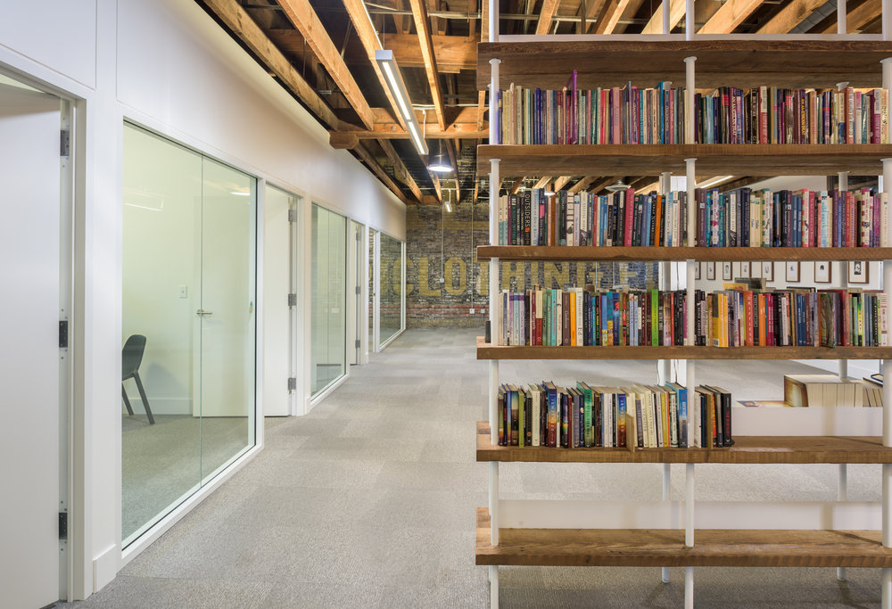 Custom metal and wood bookshelves in modern office space by Christian Dean Architecture.