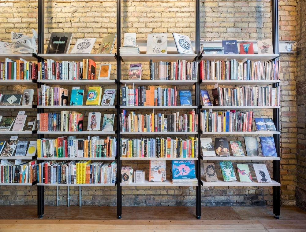 modern open steel and wood bookshelves against aged brick wall in milkweed bookstore minneapolis