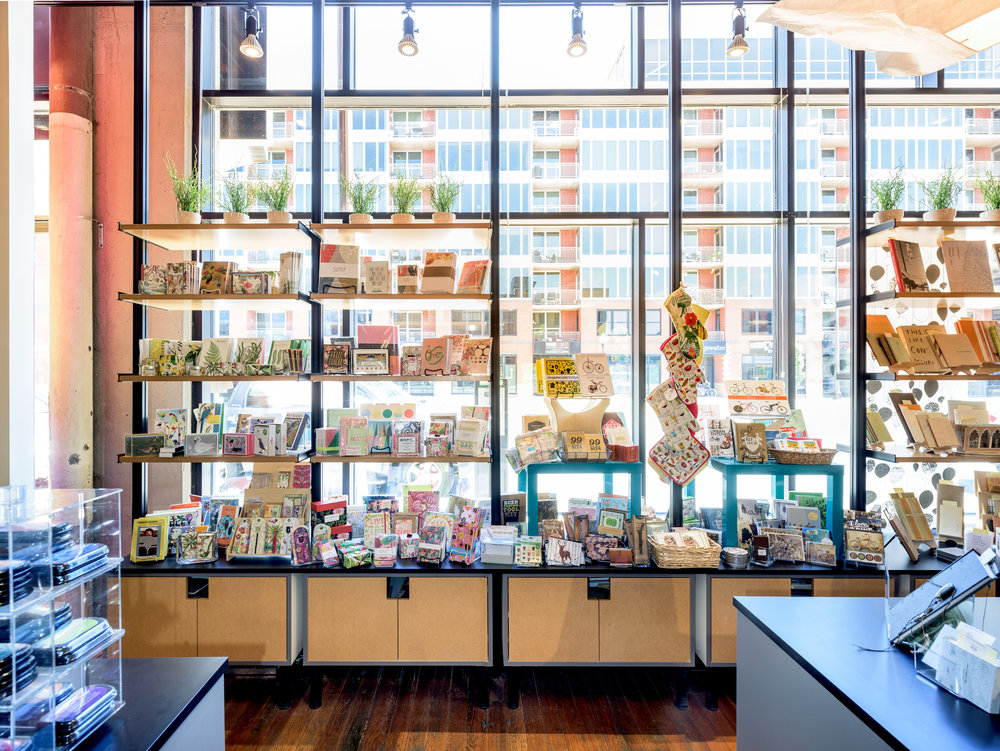 Custom steel and wood open display shelves in modern gift shop in Minneapolis.