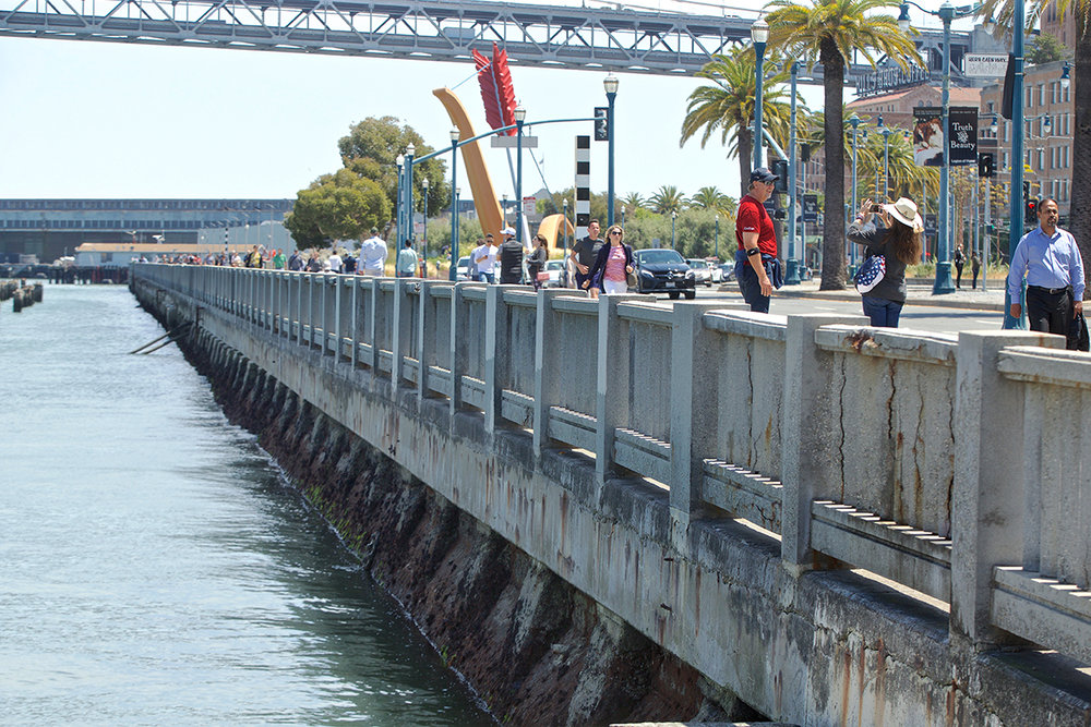 Seawall - Kevin N. Hume, SF Examiner - People walk along the Embarcadero near Pier 14 on Friday, July 20, 2018.jpg