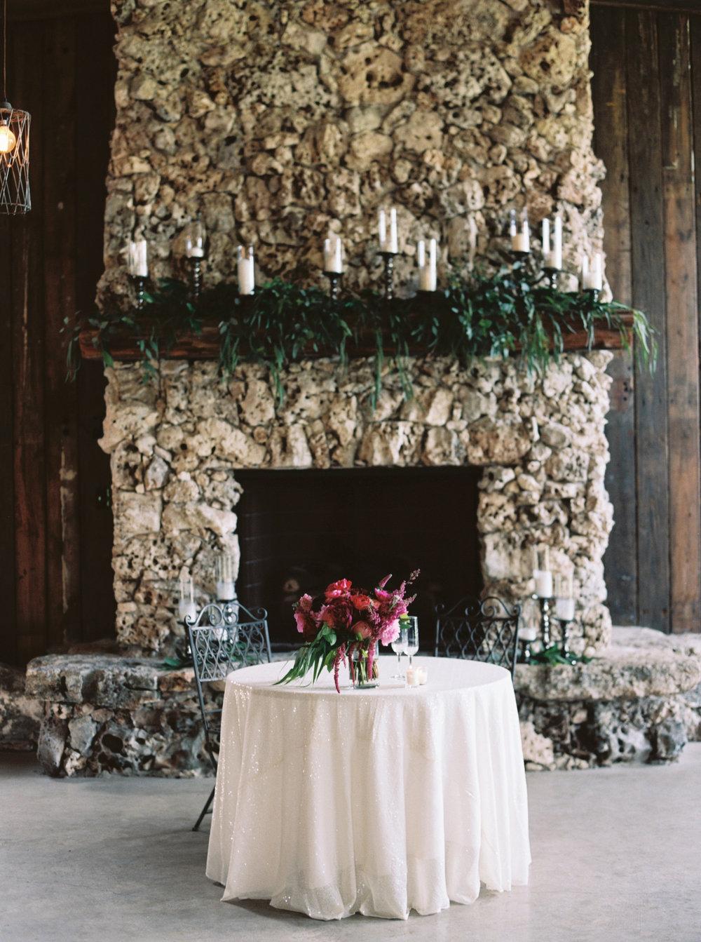 the-creek-haus-petal-pushers-sweetheart-table-fireplace-wedding-venue-vista-west-ranch