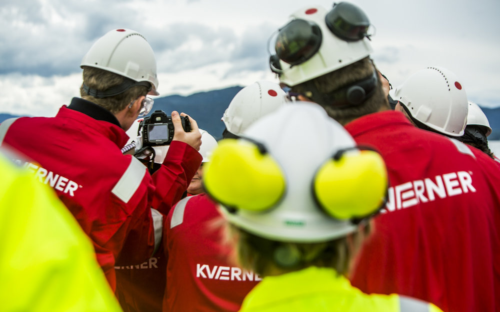 At Kværner onshore facility everyone has to change to red jumpsuits. Suddenly a brief moment of confusion happens when nobody can figure out who's most important. After a minute  the press figures it out and surrounds the prime minister. Helmets are important.
