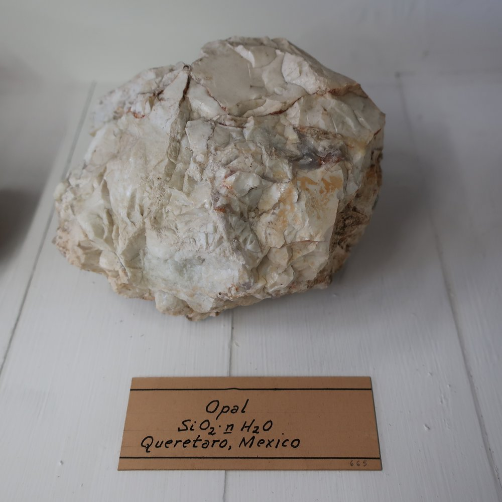 """""""Opal ,   like quartz, consists chiefly of Silica and water, but analysis generally indicates a greater quantity of the latter than in quartz, none of its varieties give fire with the steel. Specific G 2.09. This beautiful mineral is of a white bluish and yellowish white colour, and when received by transmitted light is yellow. It exhibits brilliant and changeable reflections of green, blue, yellow, and red. This play of colours has not been satisfactorily accounted for. Sir David Brewster thought it was owing to the refraction and reflection of light in certain openings in the interior of the mass, which are not fissures, but possess a uniform shape, it is translucent, fracture conchoidal and lustre resinous. Easily broken, but scratches glass. Before the blow pipe, it decrepitates and looses its colour. It consists of 90 silica and 10 water. It occurs accompanied with common opal, in porphory, & in the trap rocks of Hungary. The most splendid specemens have been brought from the province of Honduras of considerable size."""""""