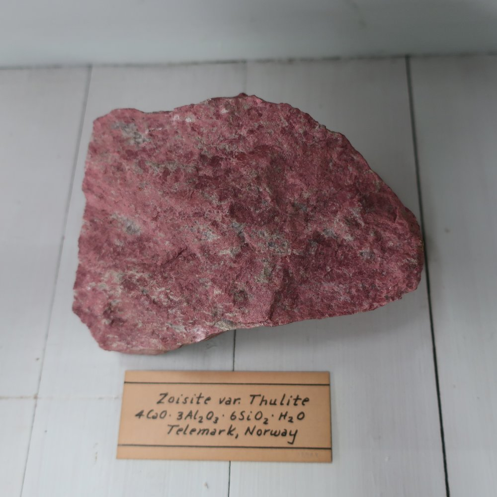 """""""Zoisite  is composed of Silica 45. Alumina 29. Lime 21. Iron 3. Sp. Gr. 3.2. It occurs in oblique rhombic prisms, of a grey, greyish, yellow, or brown colour, but are rarely perfect, owing to deep longitudinal stria, the terminations are often incomplete. It also occurs massive, it is met with, in Styria, & Bavaria also at several places in our own country. This species is by Mohs, and others, united with epedote from which it principally differs in colour."""""""
