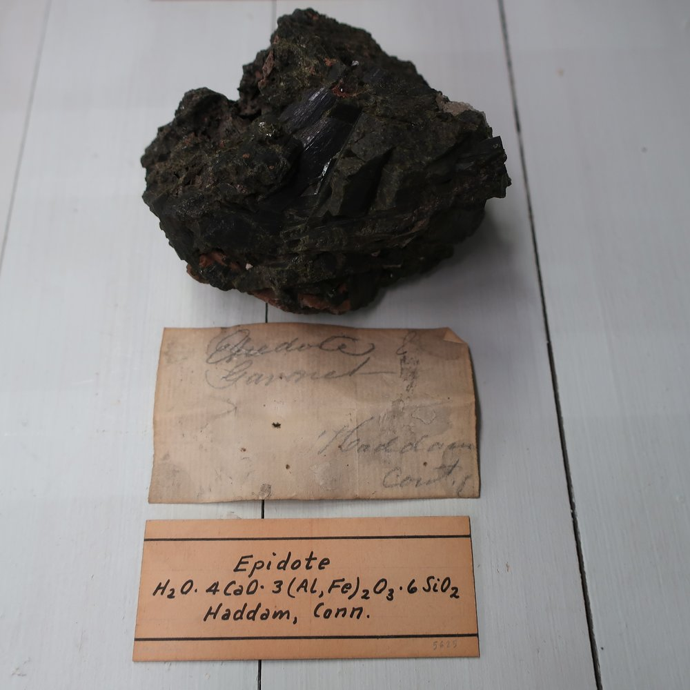 The combination of [ Epedote]  is Silica 37. Alumina 27. Lime 14 Iron 17. Sp Gr 3.42. This mineral is found granular, massive. and in prismatic crystals, variously terminated and longitudinally striated. Colour different shades of green, occasionally almost black: it has a shineing lustre. Epidote is not often found massive, but chiefly in crystals varying from acicular to an inch in diameter and several inches in length. Fine crystals occur, at Arendal in Norway, and Normark in Sweden. The magnificent crystals from these localities consist of consecutive coats, the exterior of which, admit of removal and thus out of a large imperfect crystal, one of smaller size but more completely formed may be produced with facility. It belongs principally to primitive rocks but is only found in veins and fissures, among which, in small quantities it occurs in many countries. It is found in several parts of the U States. Huge crystals occur at Lebenon N. Haup.