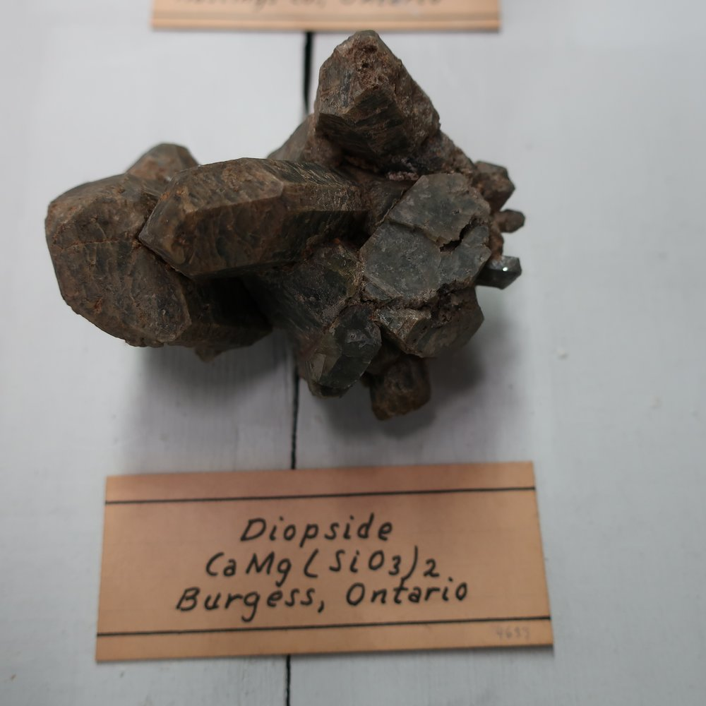 """""""Diopside  occurs in prismatic crystals, which are colourless or various shades of green, the primary is an oblique rhombic prism of the same form, and measurement, as that of augite. It is found traversing veins of Serpentine in Piedmont, latterly it has been found in Tyrol, in large crystalline masses. In the U.S., fine crystals have been in the limestone quarries of Bolton, Mass."""""""