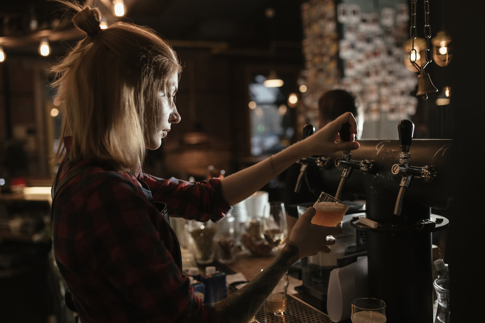 A woman in a pub pours a beer at the tap