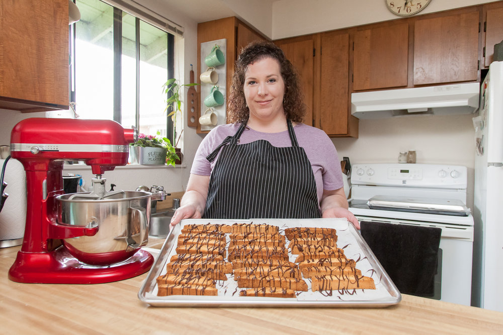 Corrina Pena in her kitchen making biscotti for her business, Frosted