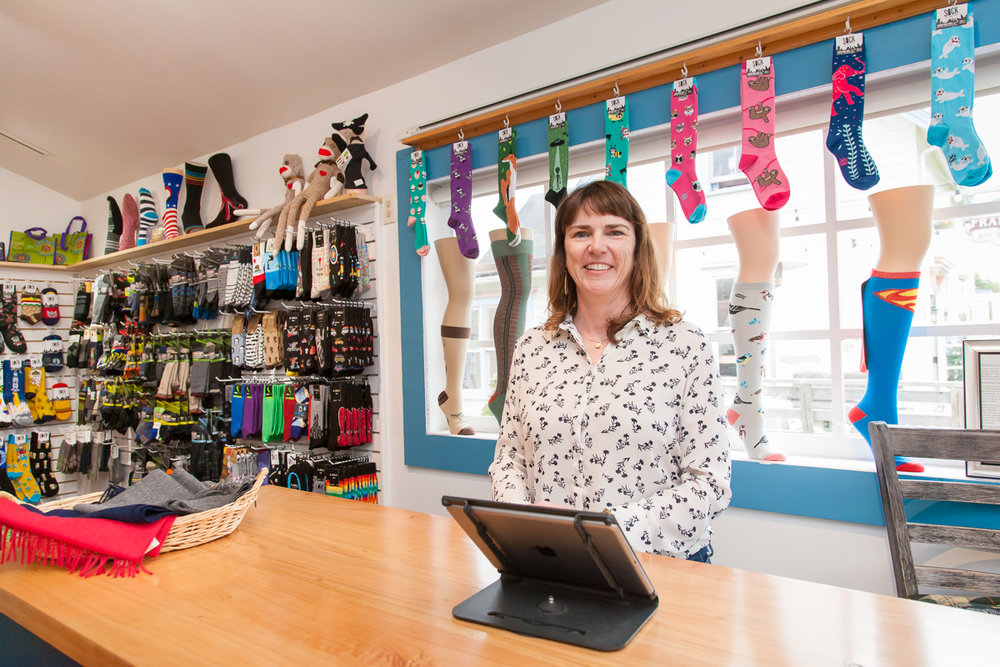 Amy Collins smiling behind the counter of her business, The Village Sock Shop in Mendocino