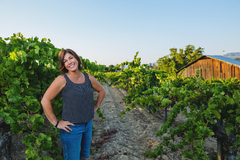 Maria Testa Martinson stands in a vineyard with a barn in the distance at Testa Vineyards, established in 1912