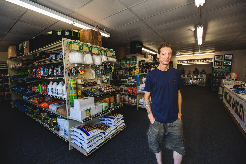 Scott Stanton stands inside his store, Willits Garden Supply, among shelves of garden products.