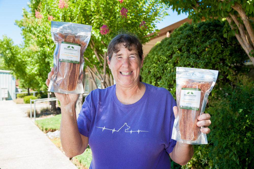 Nancy Hendricks holds up her healthy dog product with a big smile.