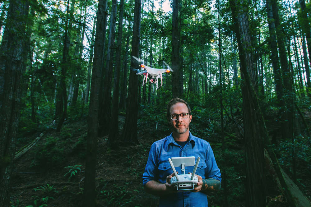 Blake Floyd Gardner flying his drone while standing in a Mendocino County redwood forest