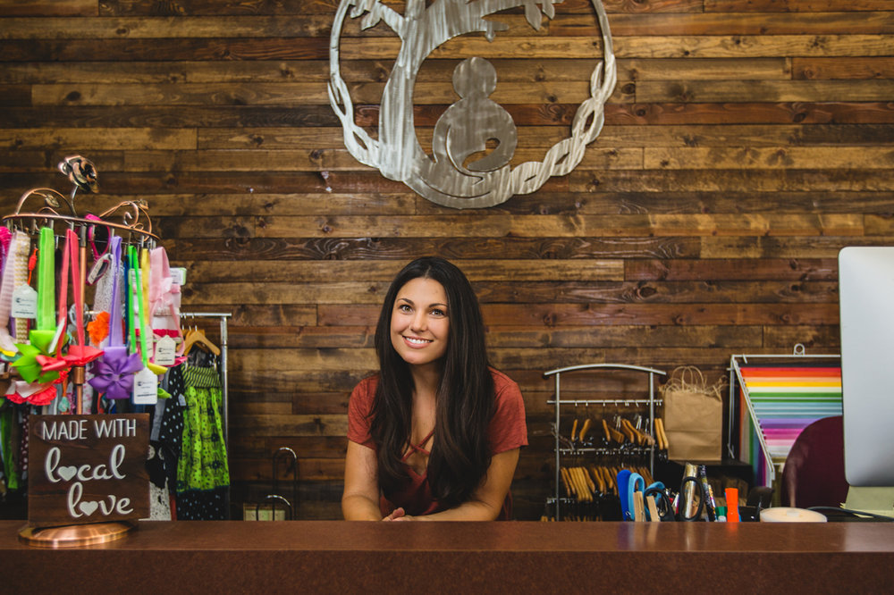 Jasmin Blanc behind the counter of her shop, Mendo Baby, in Ukiah, CA.