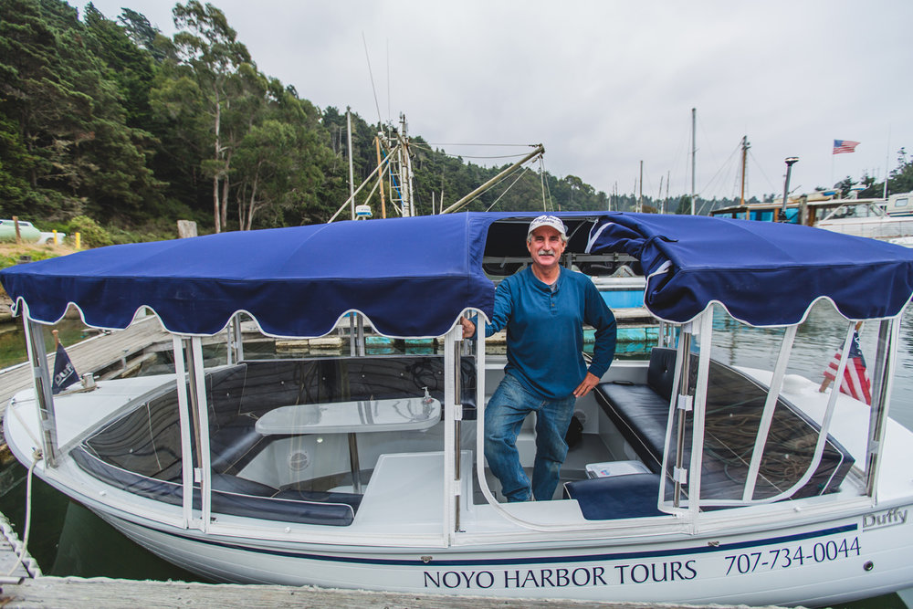 Dan Platt stands in his boat with Noyo Harbor Tours on the side, floating in Noyo Harbor, Fort Bragg, CA.