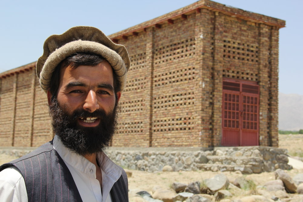 Roots-of-Peace-ROP-agriculture-Afghanistan-CHAMP-raisin-facility-brick-farmer-smile.JPG