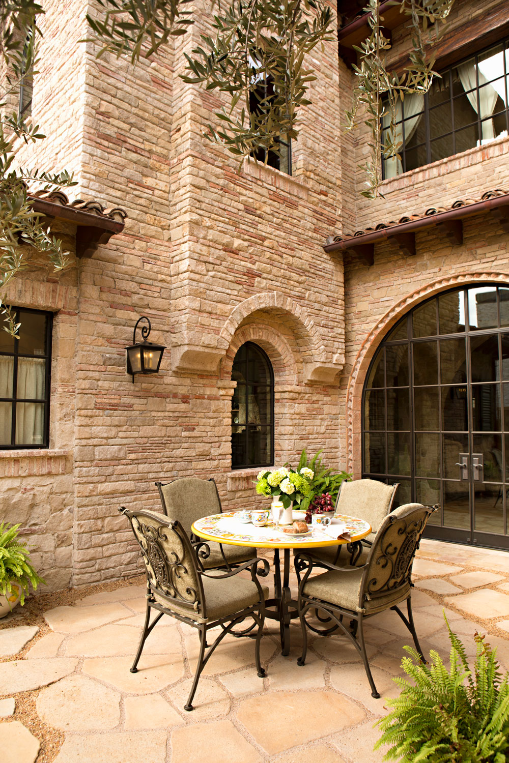 Tuscan-Mediterranean-House-Exterior-Courtyard-Patio-Table-Stone-corbin-reeves.jpg