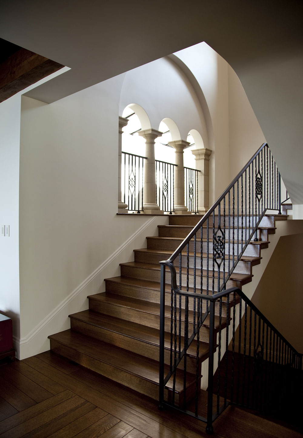 Modern-Spanish-Wood-Floor-Staircase-Wrought-Iron-Railing-Arched-Windows-Corbin-Reeves.jpg