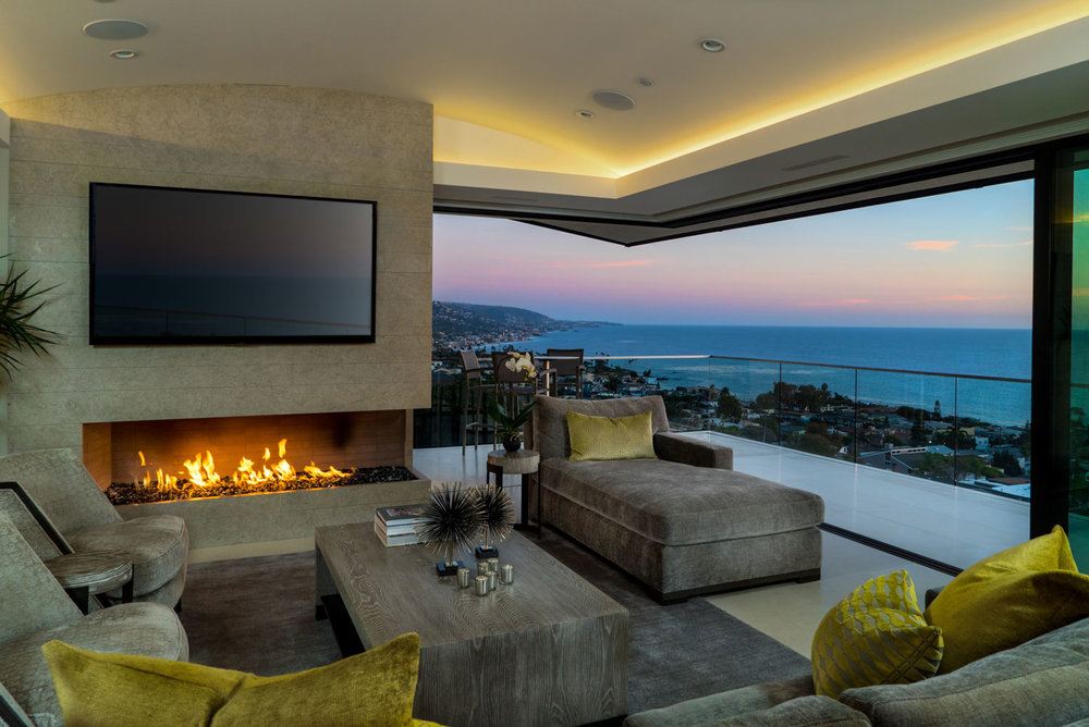 Contemporary-Living-Room-Fireplace-Retractable-Doors-Ocean-Views-Corbin-Reeves.jpg