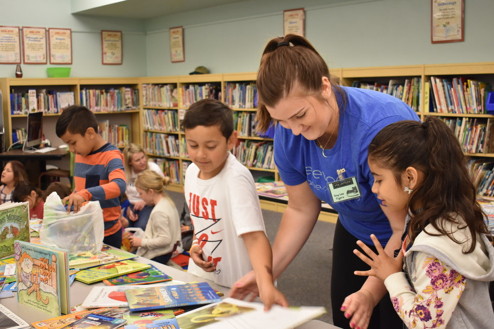 BookFest volunteer and students selecting which books to take home.