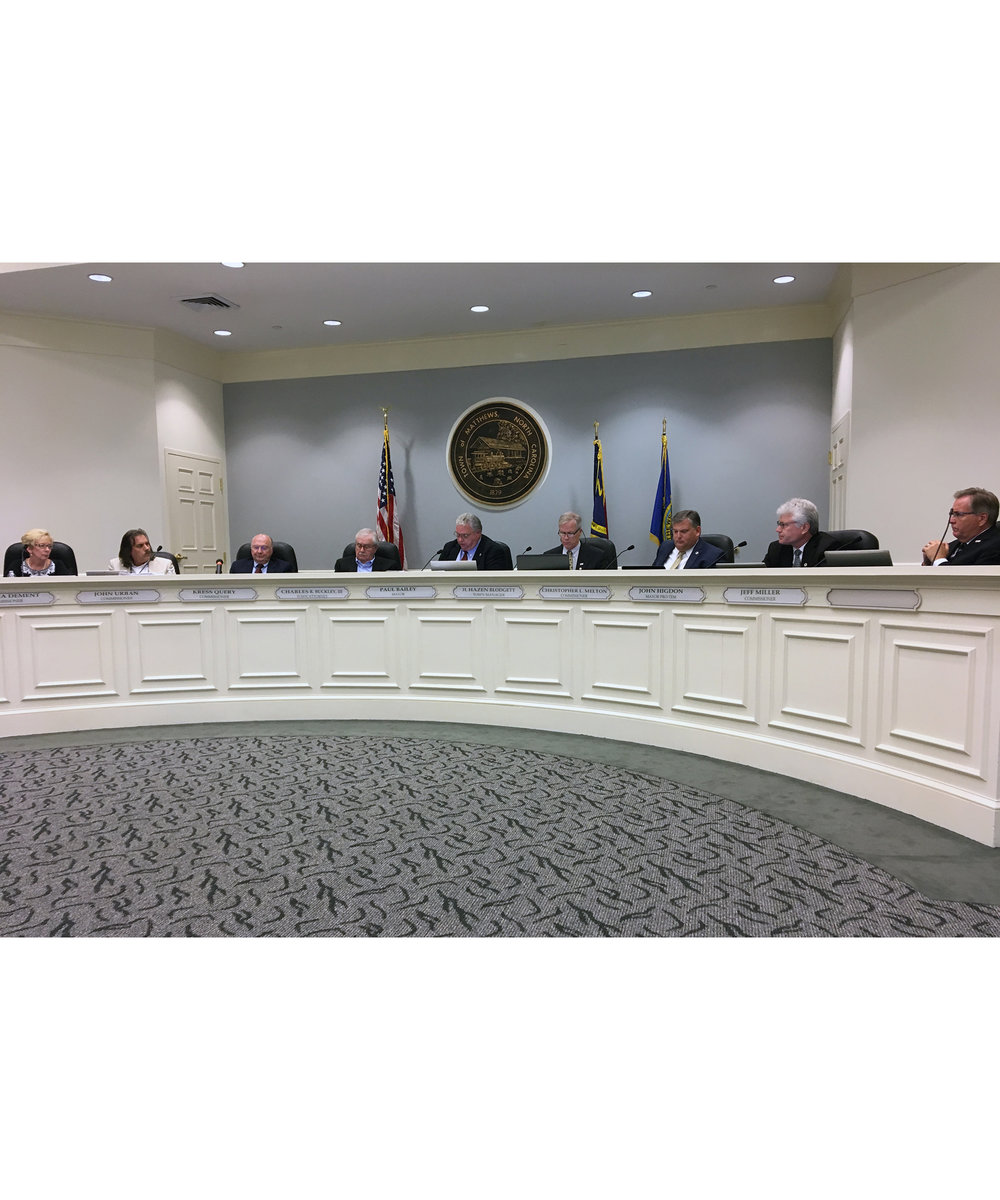 "We asked our intern, Sterling, to summarize Monday's Town Council meeting from a student's perspective. This morning's News About Town is her view of small-town government in Matthews (Or BOC meeting):I walked into a room with a large crest of Matthews, NC at the head with flags adorning each side. The mayor, Paul Bailey, was seated in the middle of a large dais with the board of commissioners circling around; I never knew that all of this was right above the Matthews library, where I had been going my whole life. The crowd included everyone from firefighters who were there in support of Kerry Ernsberger, Matthew's Employee of the Year, to a boy scout troop, who were working on their communications badge. I was surprised that the atmosphere of the meeting was both formal and casual being that it followed an ordered agenda but with the occasional joke from one of the commissioners. It was thought-provoking to see what topics were being discussed, even if most were passed unanimously; it ranged from the general issue of the effects of traffic on Matthews to the more abstract approval of Matthew's new ""vision statement"" for the future. From the concerns raised here in Matthews, I could make a connection to environmental, safety, and political concerns locally as well as nationally, despite it only being considered a small town government. At the end, I shook hands with the mayor and the assistant town manager, which is something I never envisioned myself doing as a high school student. -"